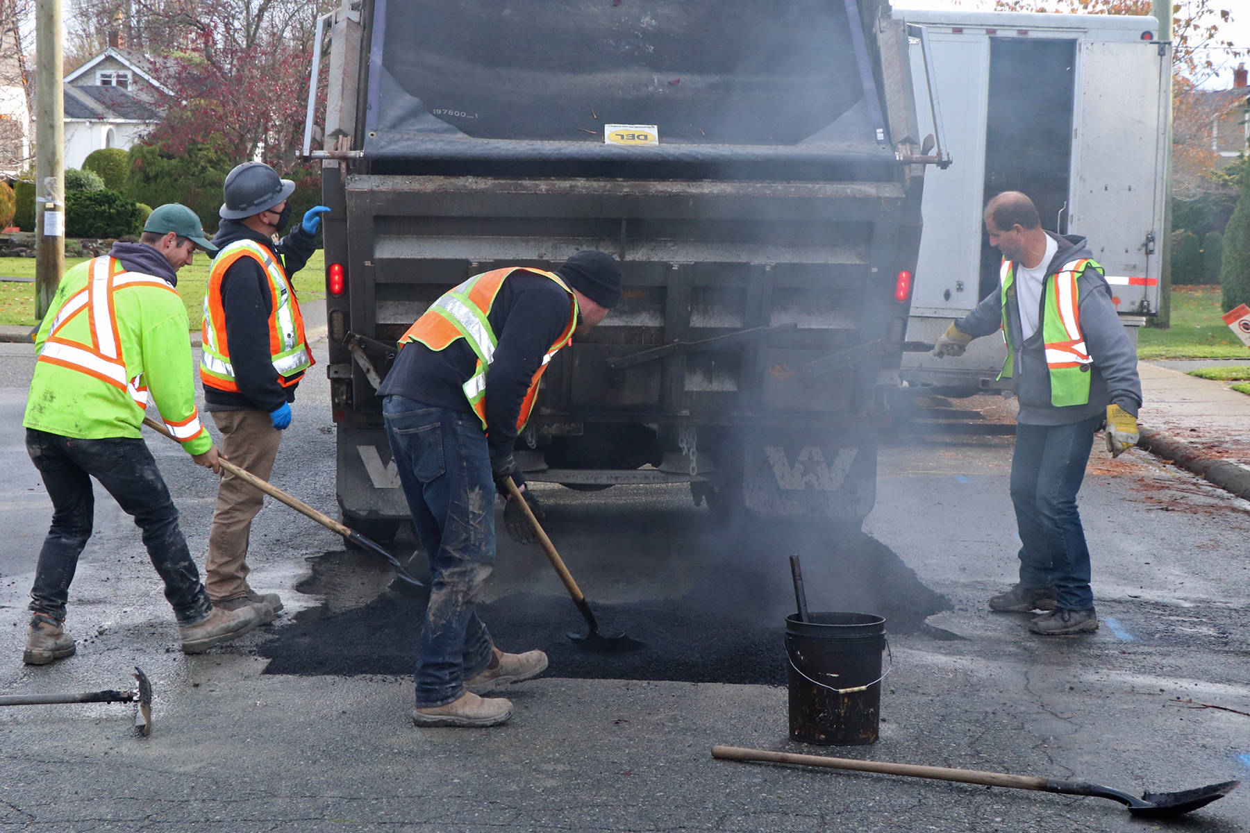An Oak Bay municipal crew finishes off a job by laying hot asphalt in place on Dalhousie Street. The District of Oak Bay is in the process of completing a number of underground infrastructure projects, part of its long term asset renewal plan for the municipality. (Don Descoteau/News Staff)